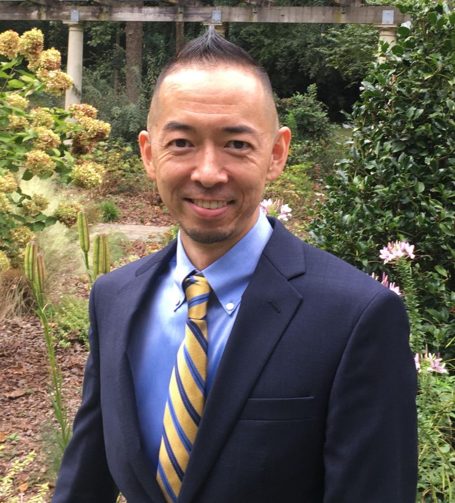 A young Japanese man smiling with a mohawk wearing a dark blue suit with yellow and stripe tie as well as light blue dress shirt standing behind the flowers in the background.
